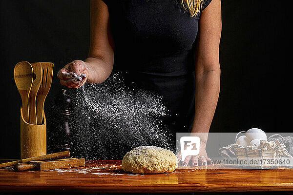 Frau bestreut Brotteig mit Mehl