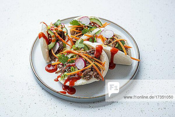 Gedämpfte Bao-Brötchen mit gewürzter Jackfrucht  Gemüse und Siracha-Sauce