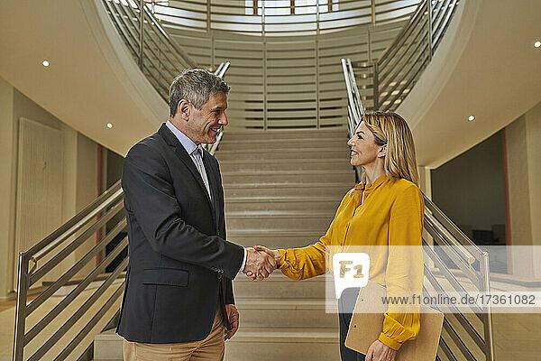 Männliche und weibliche Geschäftspartner beim Händeschütteln im Büro
