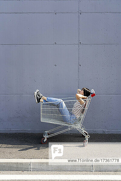 Woman with hands behind head relaxing in shopping cart