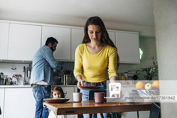 Frau reinigt Tisch  während Familie im Hintergrund zu Hause