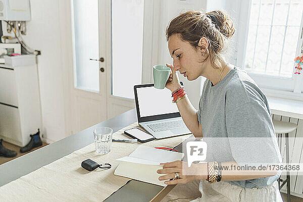Weibliche Fachkraft hält Kaffeetasse beim Lesen eines Buches in einer Wohnung