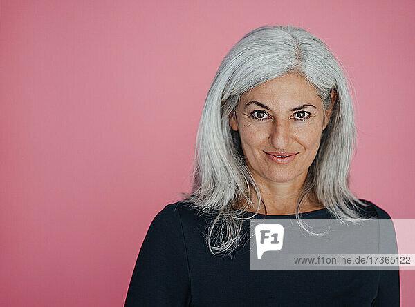 Lächelnde Geschäftsfrau vor rosa Hintergrund