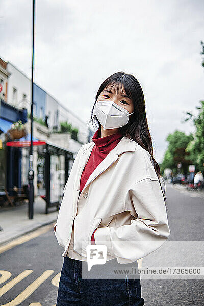 Young woman with hands in pockets wearing protective face mask in city