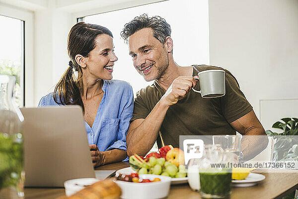 Frau sieht Mann mit Tasse beim Frühstück an
