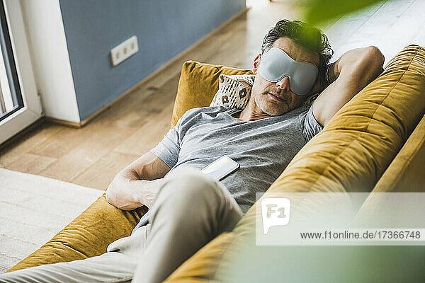 Man relaxing on sofa wearing eye mask at home