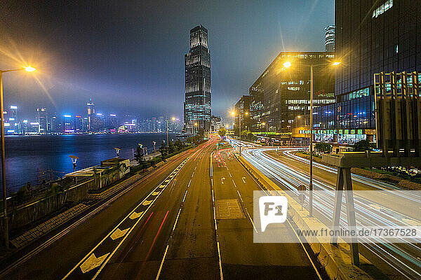 Long exposure of traffic moving on city street with residential buildings in background  Hong Kong Long exposure of traffic moving on city street with residential buildings in background, Hong Kong