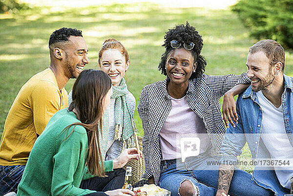 Glückliche junge Freunde beim Picknick im öffentlichen Park