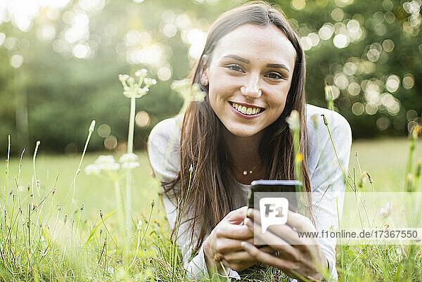 Porträt einer jungen Frau  die ihr Smartphone benutzt  während sie im Park liegt