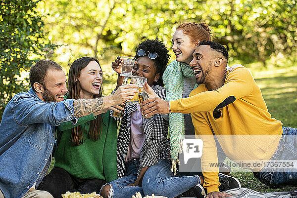 Fröhliche junge Freunde stoßen mit Getränken im Garten an Fröhliche junge Freunde stoßen mit Getränken im Garten an