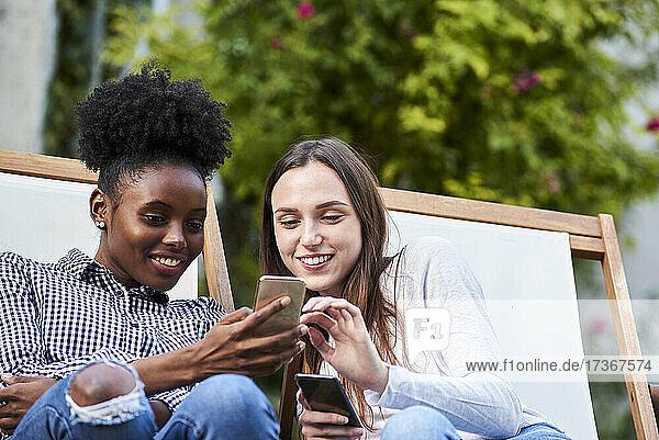 Lächelnde junge Freunde benutzen Smartphones im Park