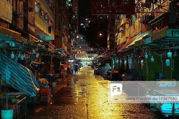 Blick auf eine Straße und einen halbgeschlossenen Marktstand bei Nacht in Hongkong Blick auf eine Straße und einen halbgeschlossenen Marktstand bei Nacht in Hongkong