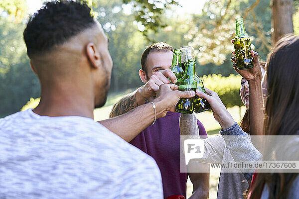 Junge Freunde trinken Bier  während sie im Park stehen Junge Freunde trinken Bier, während sie im Park stehen