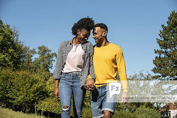 Lächelndes junges Paar mit Händchenhalten im öffentlichen Park Lächelndes junges Paar mit Händchenhalten im öffentlichen Park