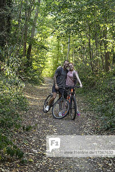 Lächelndes junges Paar steht mit Fahrrädern im Wald