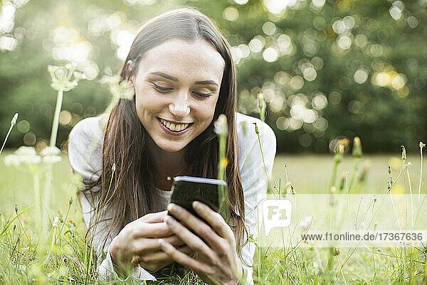 Junge Frau benutzt ihr Smartphone  während sie im Park liegt
