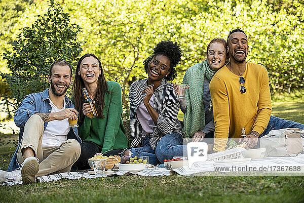 Porträt von lächelnden jungen Freunden beim Picknick im öffentlichen Park