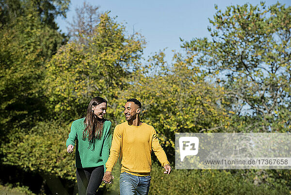 Smiling young couple walking in public park Smiling young couple walking in public park