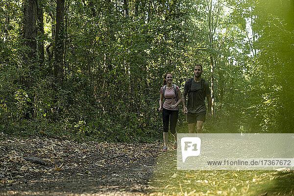 Lächelndes junges Paar beim Spaziergang im Wald Lächelndes junges Paar beim Spaziergang im Wald