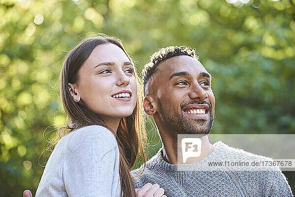 Lächelndes junges Paar im öffentlichen Park sitzend