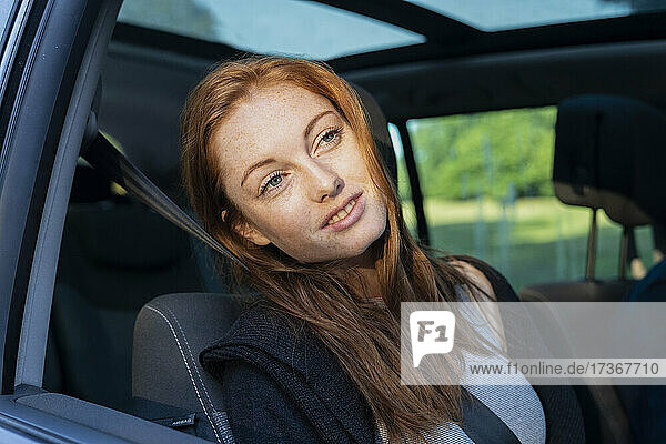 Lächelnde junge Frau im Auto sitzend