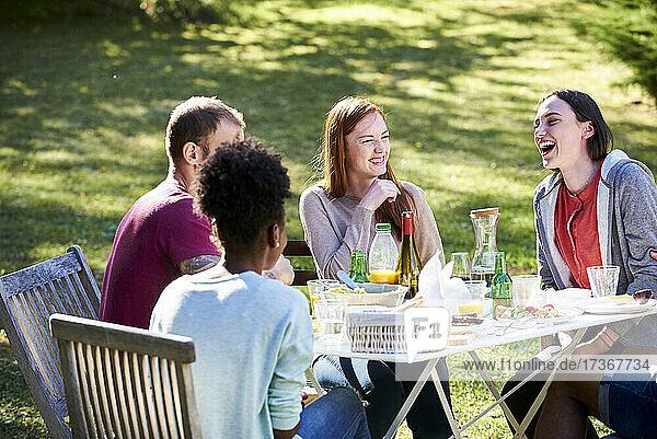 Lächelnde junge Freunde  die im Park das Essen genießen Lächelnde junge Freunde, die im Park das Essen genießen
