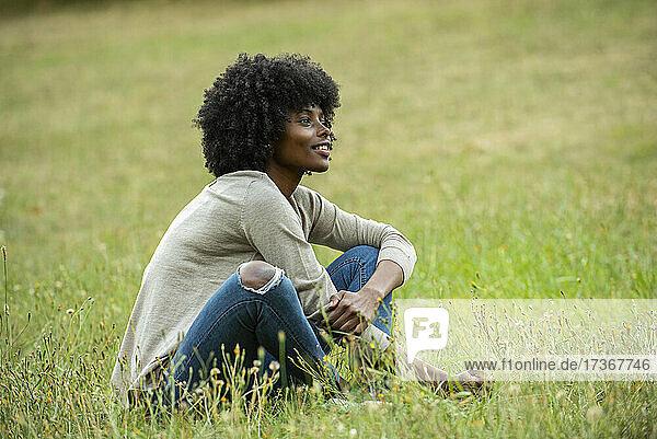Nachdenkliche junge Frau sitzt im Park