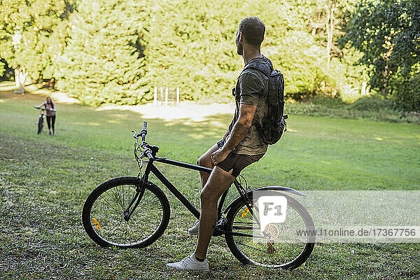 Young man sitting on bicycle while relaxing in forest Young man sitting on bicycle while relaxing in forest