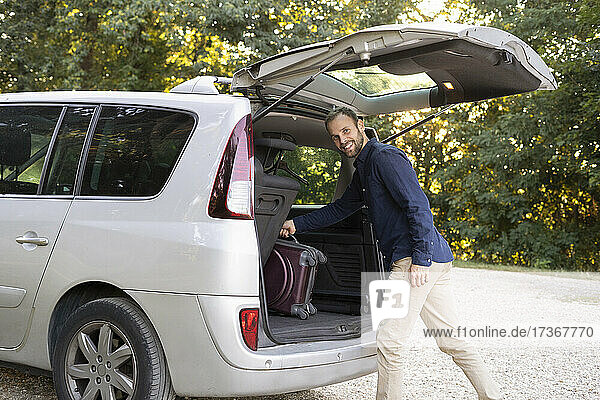 Young man loading bag in car trunk before a trip Young man loading bag in car trunk before a trip