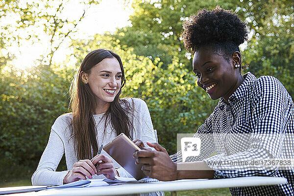 Lächelnde junge Freunde  die ein digitales Tablet benutzen  während sie im Park lernen  Orgeval