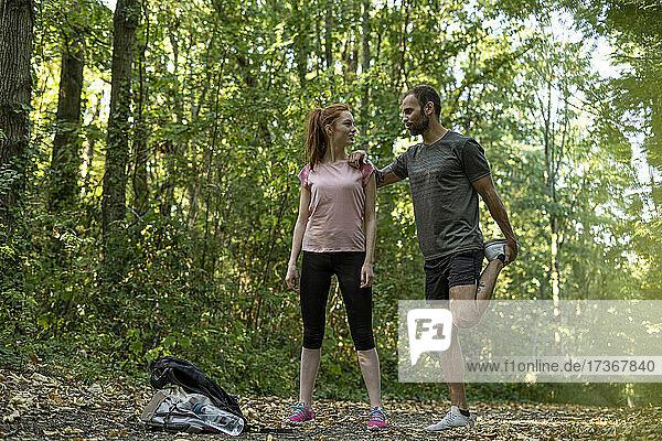 Junges Paar trainiert auf einem Weg im Wald Junges Paar trainiert auf einem Weg im Wald