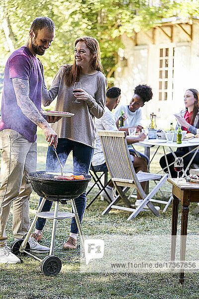 Junger Mann bereitet Essen am Grill zu  während seine Freunde am Tisch im Hintergrund sitzen Junger Mann bereitet Essen am Grill zu, während seine Freunde am Tisch im Hintergrund sitzen