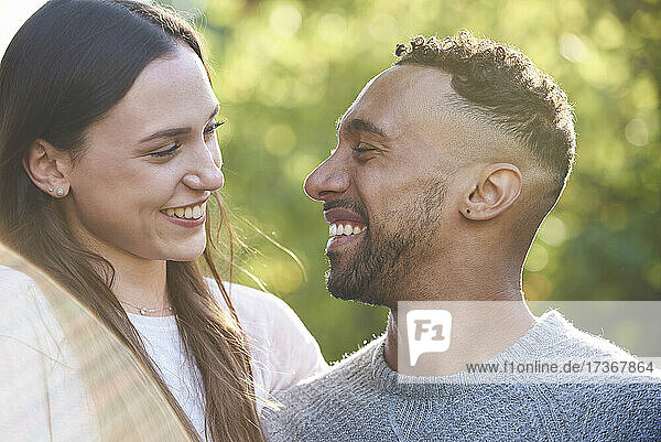Close-up of smiling young couple looking at each other in public park Close-up of smiling young couple looking at each other in public park