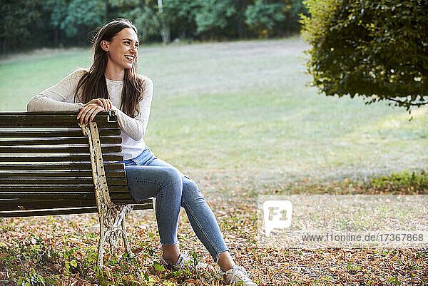 Lächelnde junge Frau sitzt auf einer Bank im Park