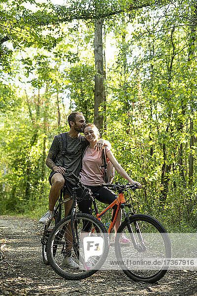 Junger Mann küsst Frau auf den Kopf  während er mit Fahrrädern im Wald steht Junger Mann küsst Frau auf den Kopf, während er mit Fahrrädern im Wald steht
