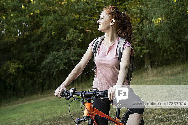 Smiling young woman sitting on bicycle in forest Smiling young woman sitting on bicycle in forest
