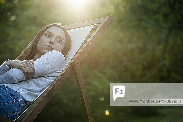 Nachdenkliche junge Frau mit verschränkten Armen an einen Stuhl gelehnt
