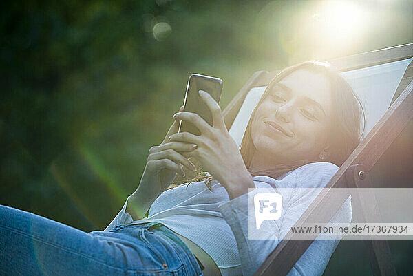 Junge Frau benutzt Smartphone im Park Junge Frau benutzt Smartphone im Park