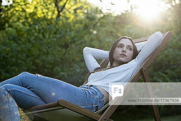 Nachdenkliche junge Frau mit Händen hinter dem Kopf auf einen Stuhl gestützt Nachdenkliche junge Frau mit Händen hinter dem Kopf auf einen Stuhl gestützt