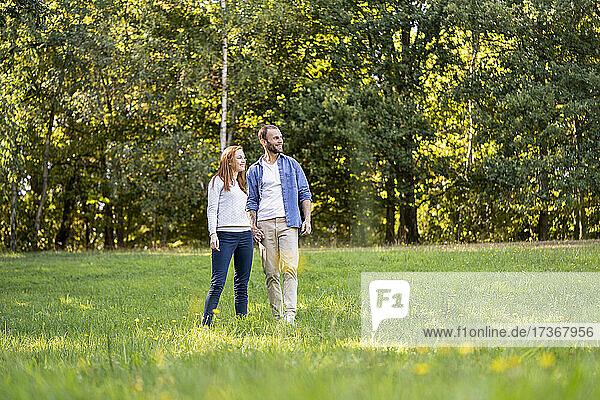 Lächelndes junges Paar bei einem Spaziergang in einem Park Lächelndes junges Paar bei einem Spaziergang in einem Park