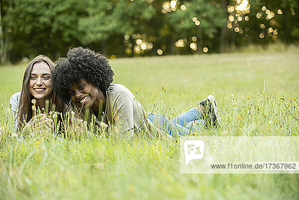 Lächelnde junge Freundinnen liegen im Park