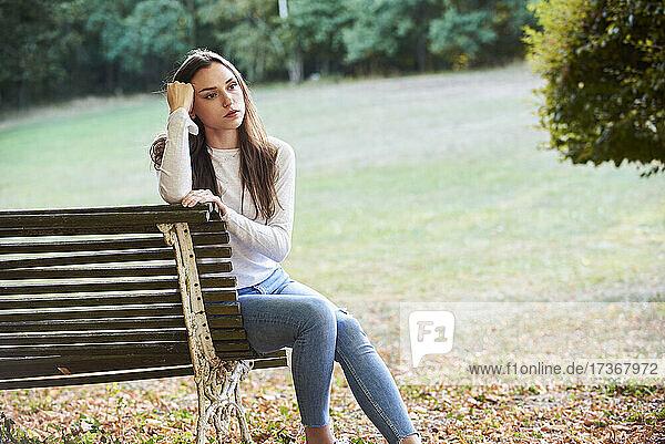 Nachdenkliche junge Frau sitzt auf einer Bank im Park Nachdenkliche junge Frau sitzt auf einer Bank im Park