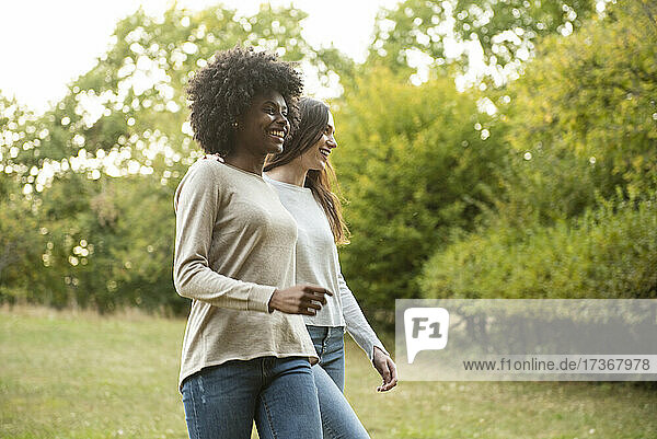 Lächelnde junge Freundinnen gehen im Park spazieren Lächelnde junge Freundinnen gehen im Park spazieren