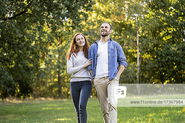 Lächelndes junges Paar hat Spaß beim Spaziergang im Park