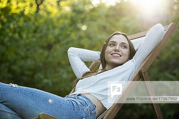 Lächelnde junge Frau mit Händen hinter dem Kopf auf einen Stuhl gestützt
