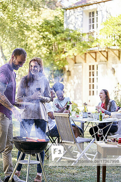 Young man preparing food in barbecue grill while his friends having drinks in background Young man preparing food in barbecue grill while his friends having drinks in background