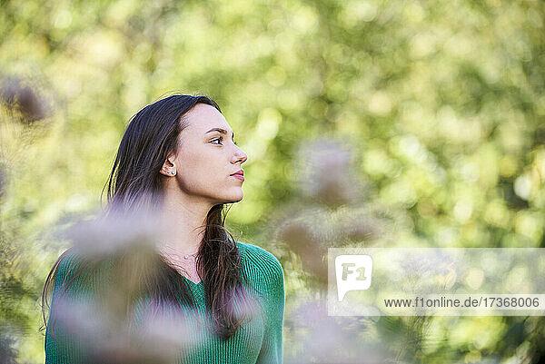 Nachdenkliche junge Frau im öffentlichen Park stehend