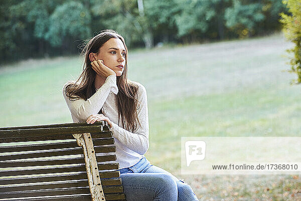 Thoughtful young woman sitting on bench in park Thoughtful young woman sitting on bench in park