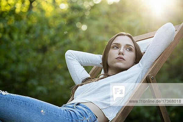 Nachdenkliche junge Frau mit Händen hinter dem Kopf auf einen Stuhl gestützt