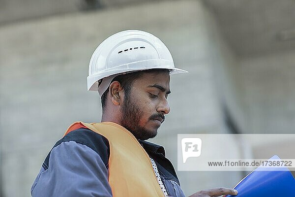 Young technician with beard working outside with helmet  Baden-Württemberg  Germany  Europe Young technician with beard working outside with helmet, Baden-Württemberg, Germany, Europe